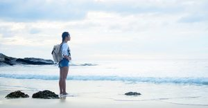 young hiker standing on a beautiful beach during a gap year.