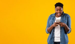 woman smiling looking at phone on yellow background